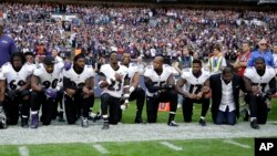 Baltimore Ravens players, including former player Ray Lewis, second from right, kneel down during the playing of the U.S. national anthem before an NFL football game against the Jacksonville Jaguars at Wembley Stadium in London, Sunday Sept. 24, 2017.