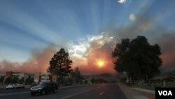 El sol se mira opacado por el humo que sale de las llamas que todavía persisten en Los Álamos, aunque los residentes de la ciudad podrán regresar a sus hogares.