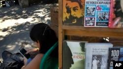 Un vendedor de libros callejero se entretiene en su teléfono inteligente, en La Habana, Cuba.