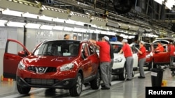 FILE - A worker is seen completing final checks on the production line at Nissan car plant in Sunderland, northern England, June 24, 2010.