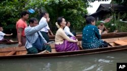 Myanmar opposition leader Aung San Suu Kyi, center, rides a boat on her way to a monastery where flood victims are sheltered, Monday, Aug. 3, 2015, in Bago, 80 kilometers (50 miles) northeast of Yangon, Myanmar. A report issued Saturday by the U.N. Offic