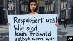 """La artista suiza Milo Moire protesta desnuda frente a la Catedral de Colonia, en el occidente de Alemania, con un cartel que dice """"Respétennos! No somos caza legal, incluso cuando estamos desnudas!!!"""". La policía de la ciudad alemana ha recibido al menos 170 denuncias de asaltos sexuales y robos durante la pasada Nochebuena. Enero 8 de 2016."""
