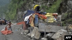 Công nhân cố gắng thu nhặt các vật dụng từ chiếc xe tải bị hư hỏng vì đất lở sau trận động đất 6.9 độ ở Gangtok, miền đông bắc Ấn Độ, ngày 20/9/2011