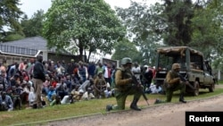 Kenyan police officers hold their position as residents watch during an operation against a gunman at the Kapenguria police station in Kapenguria, western Kenya, July 14, 2016.