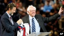 FILE - Democratic presidential candidate, Sen. Bernie Sanders, right, waves to the crowd after being presented with a shirt by Liberty President Jerry Falwell Jr., left, during a visit at Liberty University in Lynchburg, Virginia, Sept. 14, 2015.