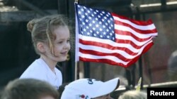 A young supporter flies a U.S. flag Feb. 28, 2016, at a rally in in Madison, Alabama, during the presidential candidates' final push to Super Tuesday.