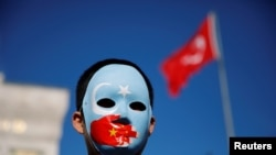 FILE - An ethnic Uighur boy wears a mask during a protest against China in Istanbul, Turkey, Dec. 14, 2019.