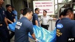 Nhân viên cứu hộ khiêng xác các nạn nhân ra khỏi công trình xây dựng nhà cao tầng ở Manila, ngày 27/1/2011