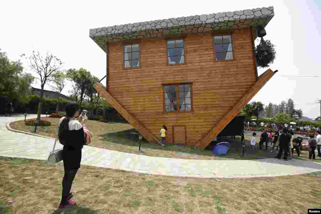 Tourists visit an upside-down house south of Shanghai, China. The house was built as a tourist attraction using everyday household items and furniture.