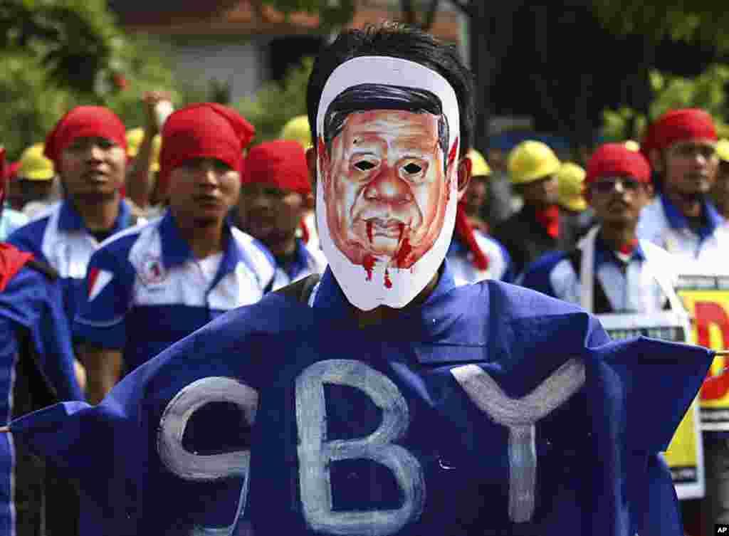 ກໍາມະກອນຄົນນຶ່ງໃສ່ໜ້າກາກທີ່ບິດບ້ຽວຂອງປະທານາທິບໍດີອິນໂດເນເຊຍ ທ່ານ Susilo Bambang Yudhoyono ໃນລະຫວ່າງການໂຮມຊຸມນຸມ ໃນວັນກໍາມະກອນສາກົນ May Day ຢູ່ນະຄອນຫລວງຈາກາຕາ. (AP Photo)