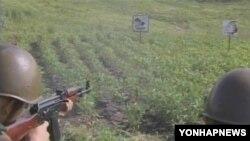 북한 인민보안국 소속 군인들이 이명박 한국 대통령의 그림과 실명이 그려진 포적지에 사격훈련을 하고 있다. '조선중앙TV' 방영.