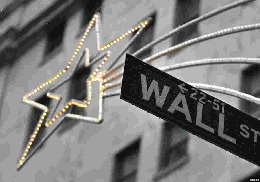 A holiday decoration is seen over Wall St. sign outside the New York Stock Exchange, November 27, 2012.