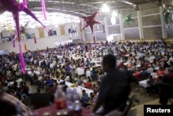 Migrants take part in a lunch event during the 10th annual celebration of migrant carnival workers in Tlapacoyan, Mexico, Dec. 14, 2015.