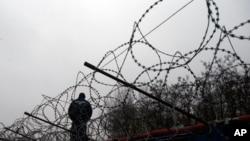 一名匈牙利警察在匈牙利和塞尔维亚边界附近的一个塞尔维亚简易难民营附近站岗。