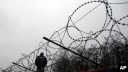 Seorang polisi Hungaria berjaga di perbatasan dekat kamp penampungan imigran di Horgos, Serbia, 8 Februari 2017 (Foto: dok).
