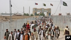 FILE - People cross the border coming from Afghanistan to Pakistan, at the border town of Chaman. Pakistan will reopen the Chaman border crossing for routine traffic on Sept. 1, 2016, after days of closure, officials said.