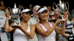 Su-Wei Hsieh of Taiwan, left, and Shuai Peng of China pose with their trophies after winning against Ashleigh Barty of Australia and Casey Dellacqua of Australia in the Women's doubles final match at the All England Lawn Tennis Championships in Wimbledon,