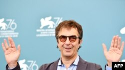 """Canadian director Atom Egoyan poses during the photocall for his film """"Guest of Honour"""" presented in competition, Sept. 3, 2019, during the 76th Venice Film Festival."""