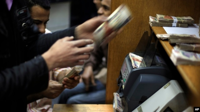 FILE - Egyptians count money at a currency exchange office in downtown Cairo, Jan. 2, 2013.