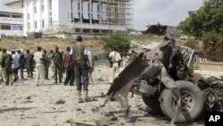 Somali soldiers stand near the twisted car-bomb that exploded near Somali parliament's headquarters, in Mogadishu, Somalia, November 7, 2012.