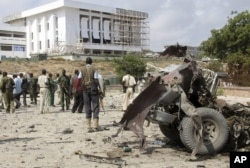 FILE - Somali soldiers stand near the twisted car-bomb that exploded near Somali parliament's headquarters, in Mogadishu, Somalia, November 7, 2012.