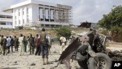 Abasirikare ba Somaliya bahagaze hafi y'inyubakwa y'inama nshingamateka, hafi y'ibisigarira vy'imodoka yaturikijwe n'umwihevyi.