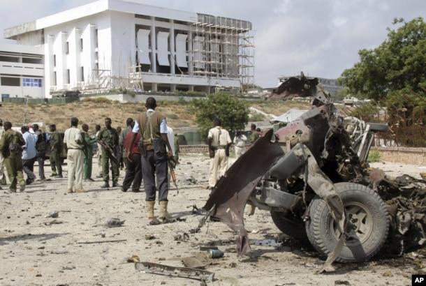 FILE - Somali soldiers stand near the twisted car-bomb that exploded near Somali parliament's headquarters, in Mogadishu, Somalia, November 7, 2012.