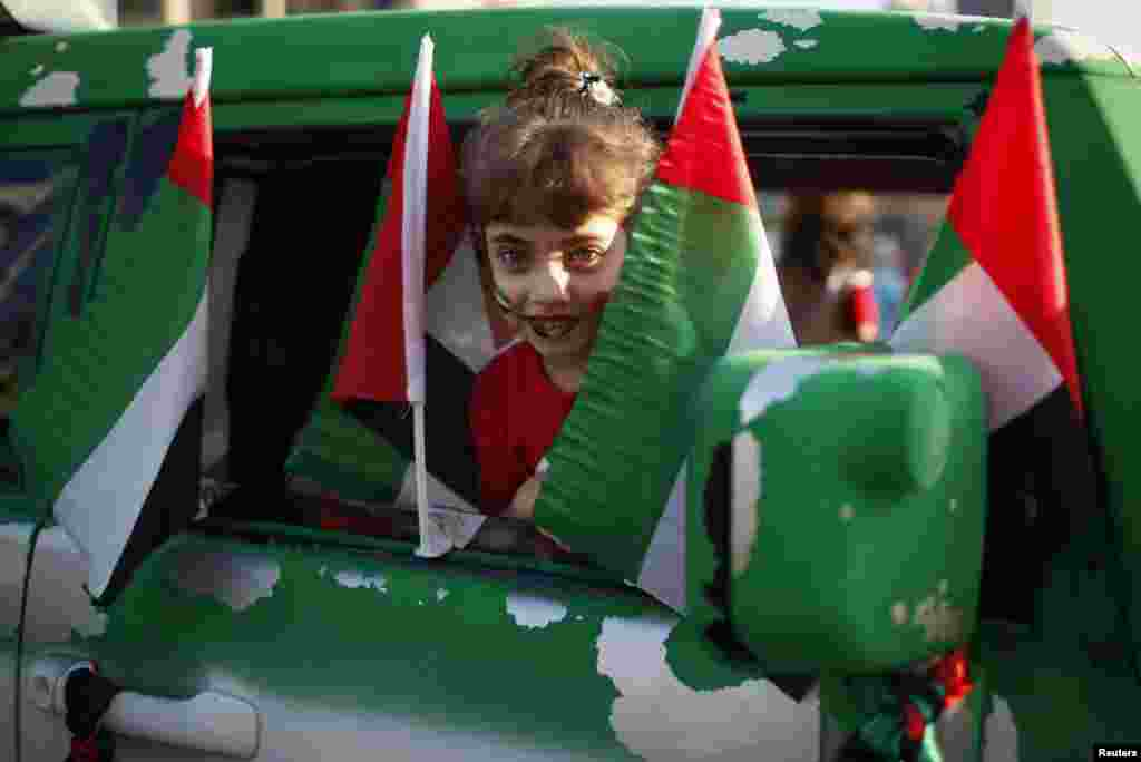 A girl looks out from a car decorated with national flags during a parade celebrating the 41st National Day of the United Arab Emirates, in downtown Dubai December 2.