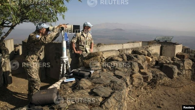 A member of the United Nations Disengagement Observer Force (UNDOF) looks through binoculars at Mount Bental, an observation post in the Golan Heights overlooking the Syrian side of the Qunietra crossing, Aug. 31, 2014.
