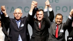 Libyan representatives from rival factions, left to right, Mohammed Chouaib, Fayez Sarraj, and Dr. Saleh Almkhozom react after signing a U.N.-sponsored deal aiming to end Libya's conflict, Dec.17, 2015 in Sikhrat, Morocco.