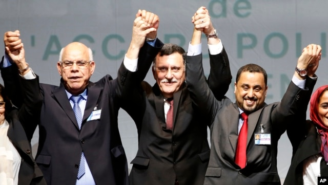 L-R, Mohammed Chouaib, head of delegation from the U.N.-recognized government in the eastern city of Tobruk, Libya, Fayez Sarraj, Libyan prime minister, and Dr. Saleh Almkhozom, second deputy chairman of the Libyan General National Congress, react after signing a U.N.-sponsored deal aiming to end Libya's conflict, Dec.17, 2015 in Sikhrat, Morocco.