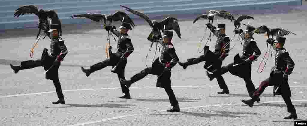 Falconers of the Mexican army hold their falcons as they march during the traditional Bastille Day military parade on the Place de la Concorde in Paris, France.