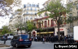 FILE - A crowd of mourners and journalists in front of the Bataclan concert hall.