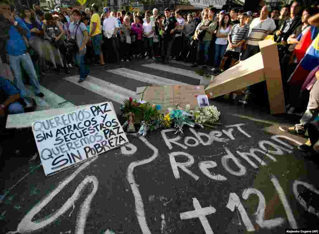 """Estudantes assistem a uma vigília para lamentar a morte de dois estudantes durante confrontos violentos em Caracas, Venezuela, na quinta-feira, 13 de fevereiro, 2014. Durante a vigília os estudantes exigiram justiça para, Bassil Da Costa e Robert Redman. O cartaz na esquerda diz: """"Nós queremos a paz, sem assaltos, seqüestros. Queremos paz sem pobreza."""""""