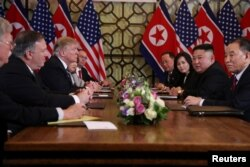 North Korea's leader Kim Jong Un and U.S. President Donald Trump attend the extended bilateral meeting in the Metropole hotel with their advisers.