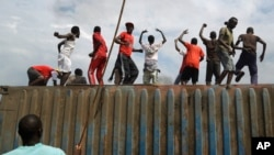 Demonstrators climb on a container they moved to use as a barricade in the Cibitoke neighborhood of Bujumbura, Burundi, May 19, 2015.