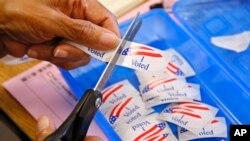 """FILE - An elections clerk cuts from a strip of """"I Voted"""" stickers at a polling place in Oklahoma City, June 28, 2016. Officials in Oklahoma, Texas and Louisiana say they've denied a request by Russian officials to be present at polling stations during next month's election."""