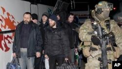 Украинский военнослужащий сопровождает пленных пророссийских сепаратистов для обмена пленными в пригороде Донецка. 26 декабря 2014 г.