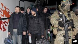 Seorang prajurit Ukraina berjalan di dekat para separatis pro-Rusia dalam pertukaran tawanan perang di dekat Donetsk Ukraina timur, 26/12/2014.