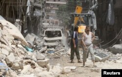 Residents inspect a damaged site after an airstrike on Aleppo's rebel held Al-Mashad neighborhood, July 26, 2016.