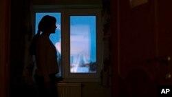 ARHIVA - Žena koju je tukao suprug gleda kroz prozor sigurne kuće za žene žrtve porodičnog nasilja (Foto: AP/Pavel Golovkin)