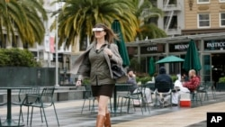 Yvonne Felix, of Canada, wears eSight electronic glasses and walks through Union Square during a visit to San Francisco, Feb. 2, 2017. The glasses enable the legally blind to see.