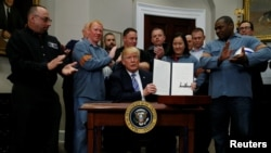 U.S. President Donald Trump, surrounded with American workers, shows a proclamation to establish tariffs on imports of steel and aluminum at the White House in Washington, March 8, 2018. (REUTERS/Leah Millis)
