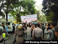 Kelompok yang mengatasnamakan warga menolak kegiatan Jalsah Salanah dari kelompok Ahmadiyah di Bandung akhir September 2018 sementara polisi nampak berjaga. (Courtesy: LBH bandung)