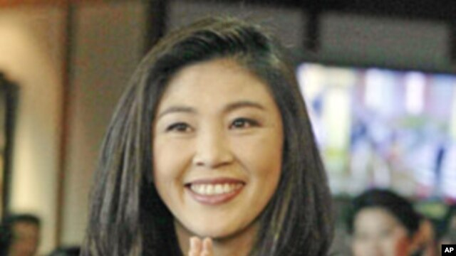 "Thailand's new Prime Minister Yingluck Shinawatra gives a Thai traditional ""wai"" greeting at parliament in Bangkok, Aug. 5, 2011"