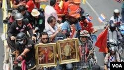 Demonstran anti-pemerintah Kaos Merah, membawa gambar raja dan ratu Thailand, meninggalkan perkemahan mereka di kawasan perdagangan kota Bangkok, 28 April 2010.