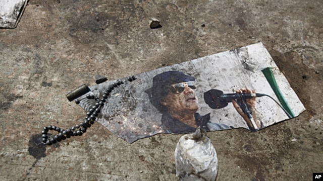 A picture of ousted Libyan leader Muammar Gadhafi is seen on the ground of the ransacked Bab al-Aziziya compound in Tripoli, August 26, 2011
