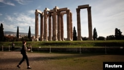A tourist makes her way at the archaeological site of the Temple of the Olympian Zeus in Athens, Greece.