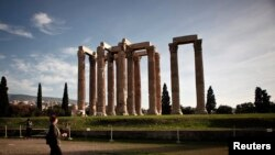FILE - A tourist makes her way at the archaeological site of the Temple of the Olympian Zeus in Athens, Greece, Nov. 18, 2014.