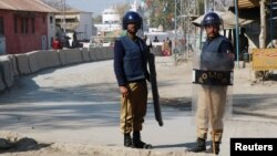 FILE - Policemen guard near the central prison where a court convicted 31 people over the campus lynching of a university student last year who was falsely accused of blasphemy, in Haripur, Pakistan, Feb. 7, 2018.